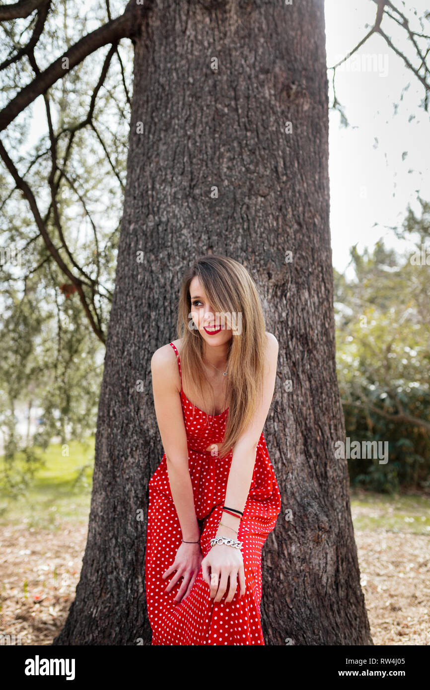 Young smiling woman with red dress leaning towards the camera Stock Photo