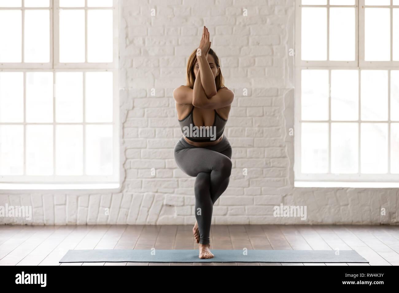 Attractive woman practicing yoga, standing in Eagle pose, Garudasana - Stock Image