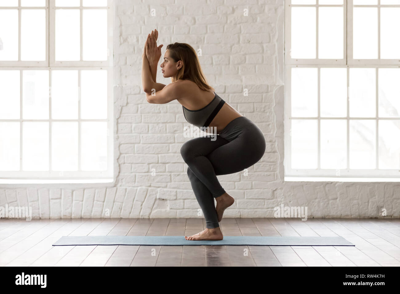 Beautiful woman practicing yoga, standing in Eagle pose, Garudasana - Stock Image