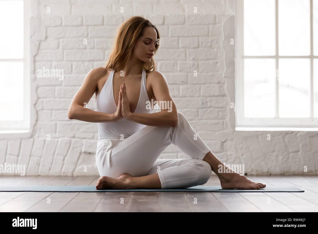 Sporty woman practicing yoga, sitting in Ardha Matsyendrasana pose - Stock Image