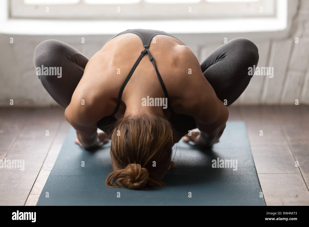 Young woman practicing yoga, sitting in Garland pose, Malasana exercise Stock Photo