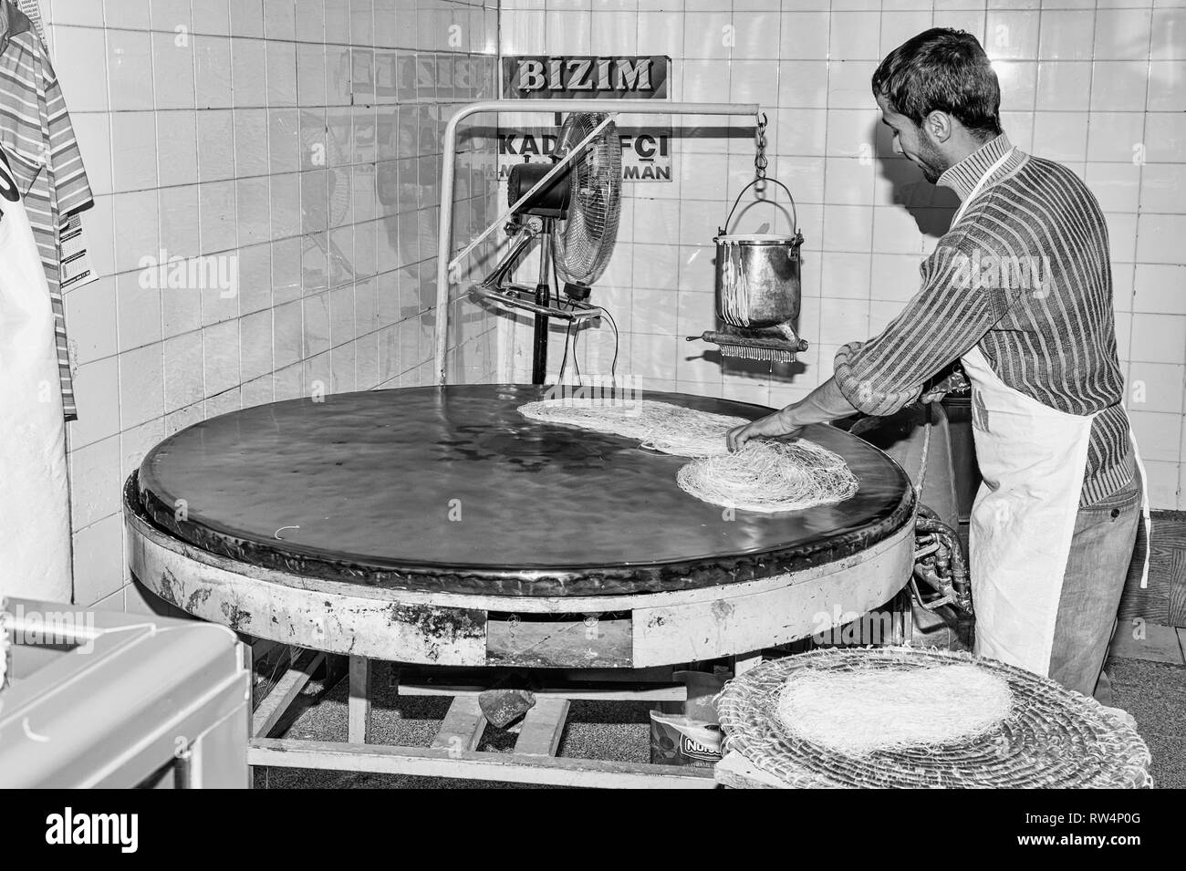 Artisan pouring a continuous stream of highly-fluid dough on a hot plate to prepare the Tel Kadayif (Angels hair), used for Künefe dessert, Antioch ma - Stock Image