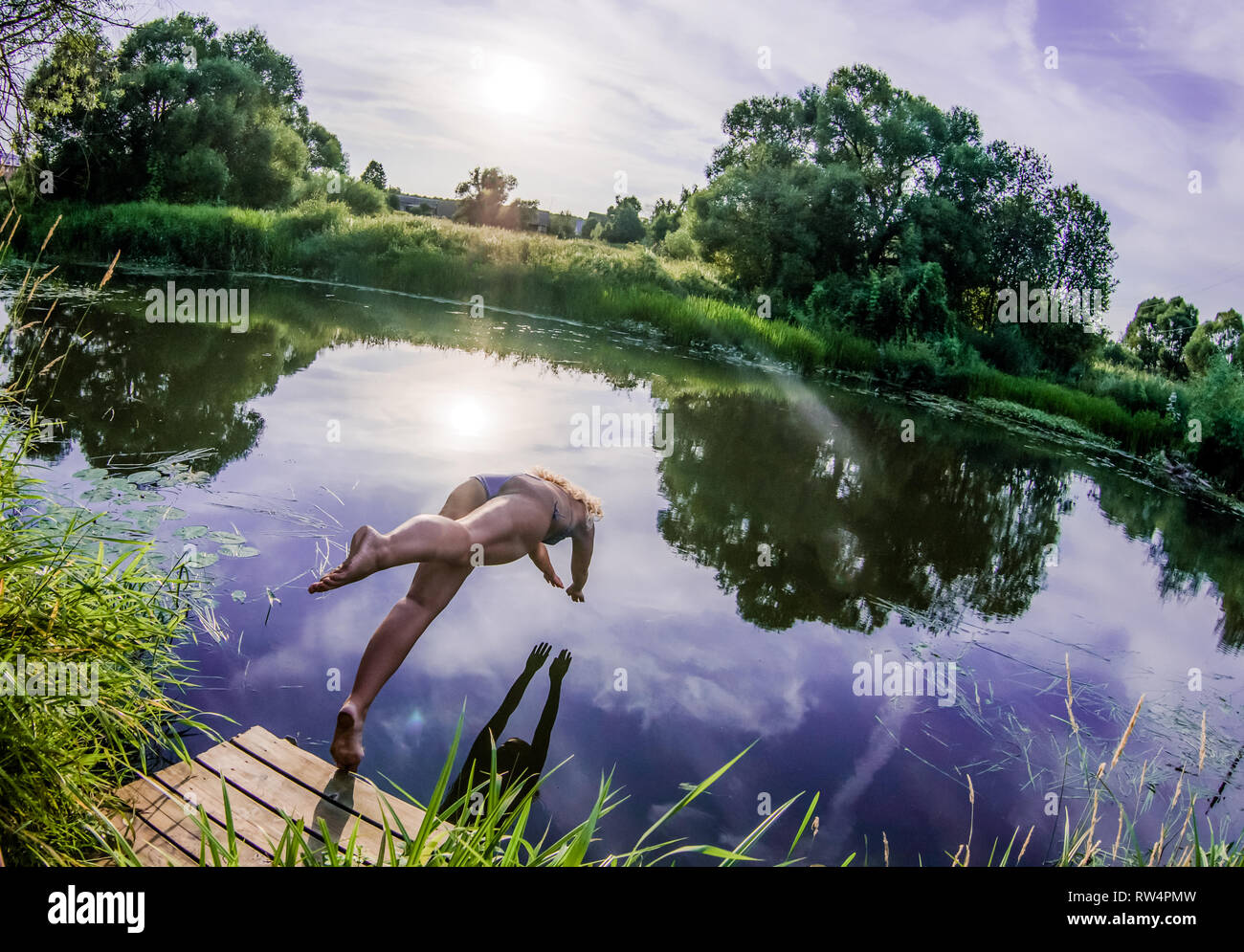 Woman jumping off wooden pier into a wild river Stock Photo