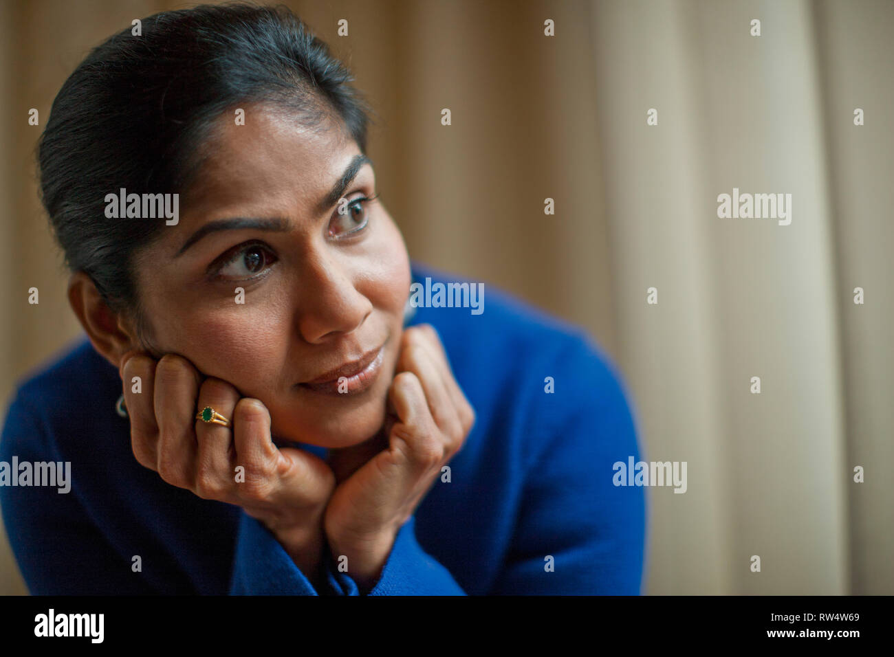 Young woman nervously waits to be called for her job interview. - Stock Image