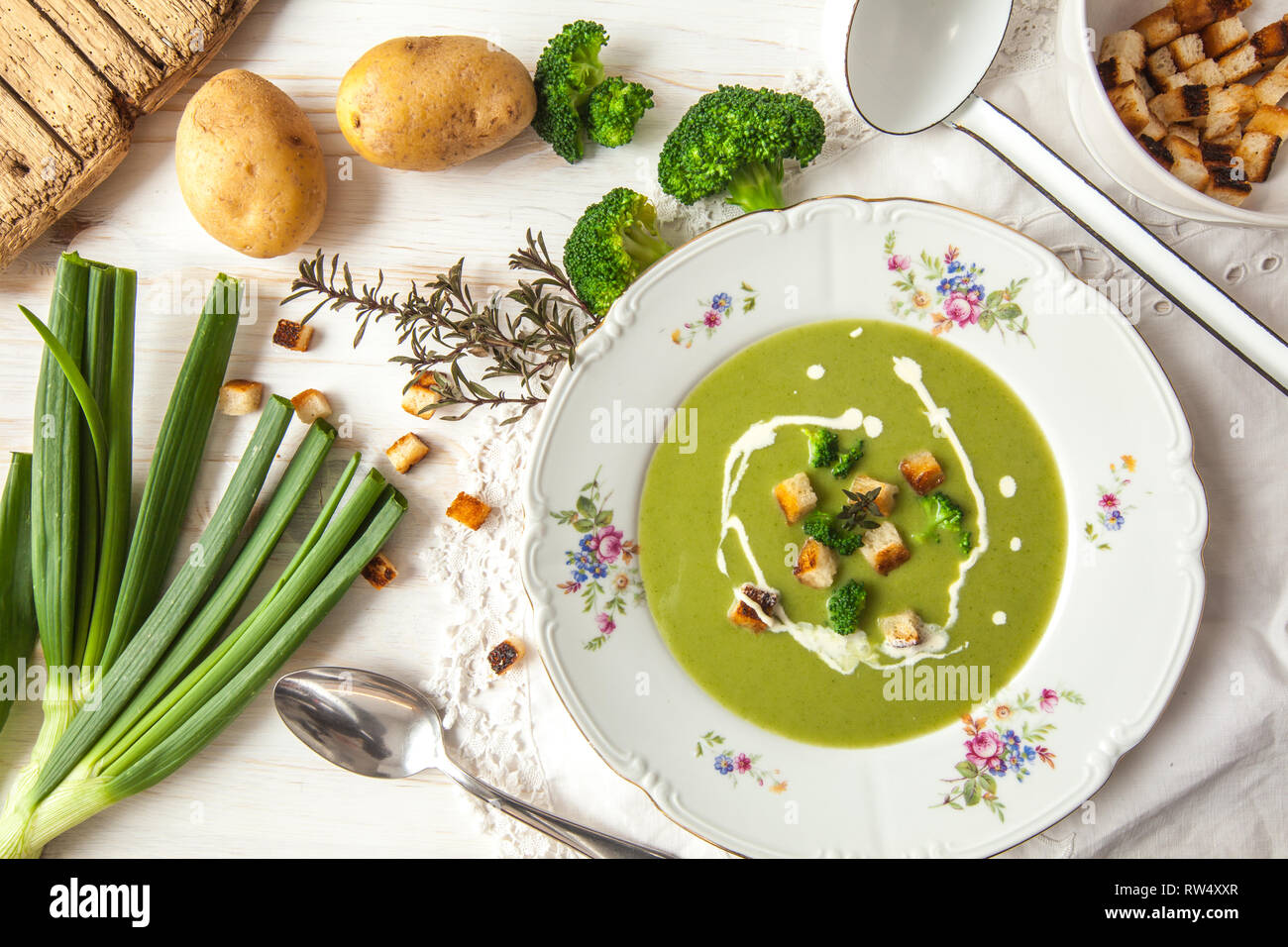 Spring detox broccoli green cream soup with potatoes and vegan cream in bowl on bright wooden board over white background, top view. Clean eating Stock Photo