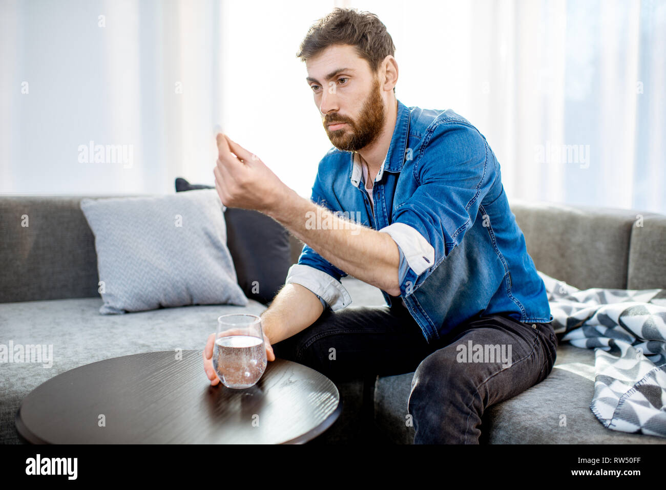 Man drinking some medicines feeling bad or having hangover after the alcohol party, sitting on the couch at home Stock Photo