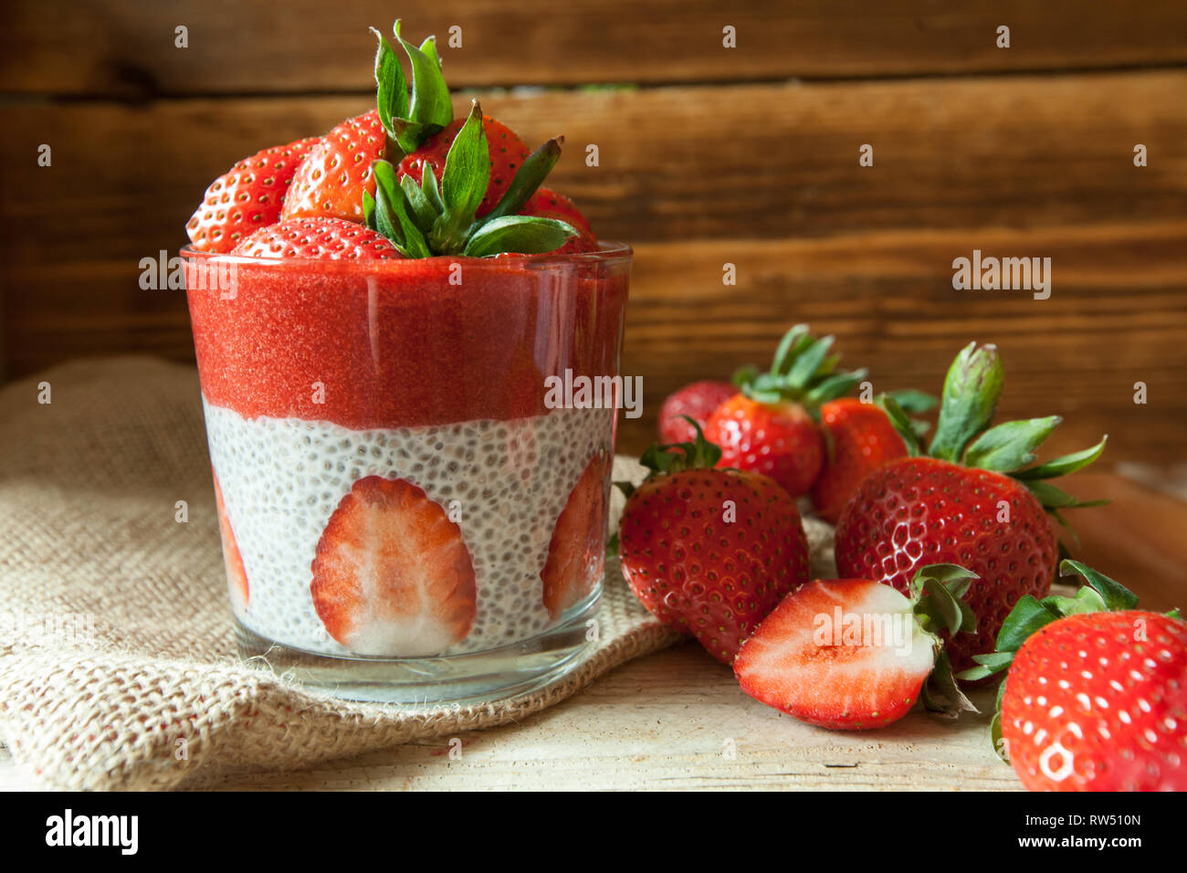 Low Carb Strawberry and chia puddings in a glass, wood background Stock Photo