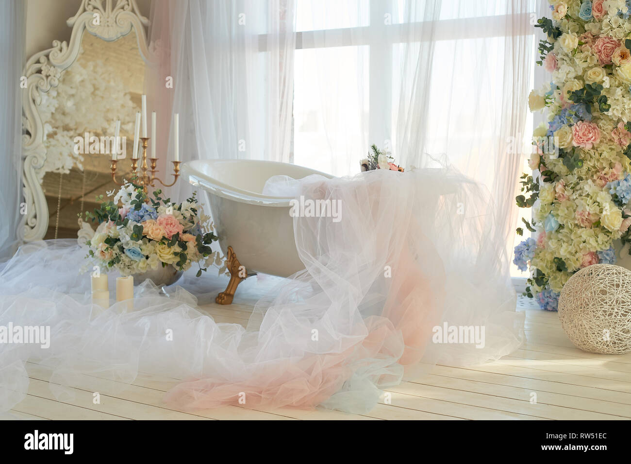 Bath on lion's Golden paws.The atmosphere of romance and love. Light interior, chiffon, flowers. - Stock Image