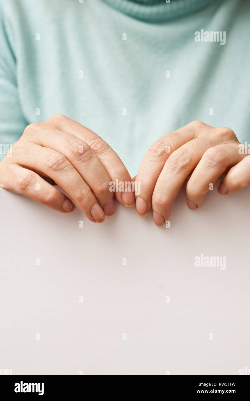 sequence images of the hands of a woman ripping a paper in half - Stock Image