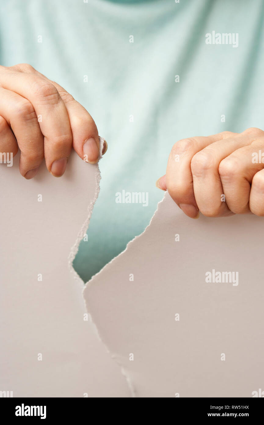 sequence images of the hands of a woman ripping a paper in half Stock Photo
