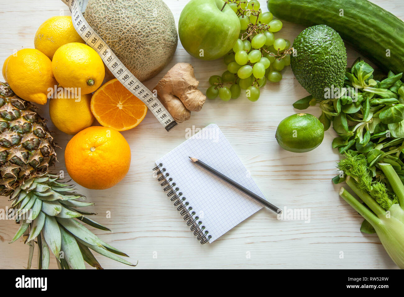 Flat lay composition with measuring tape, healthy vegetables and fruit on wooden background. Weight loss diet Stock Photo