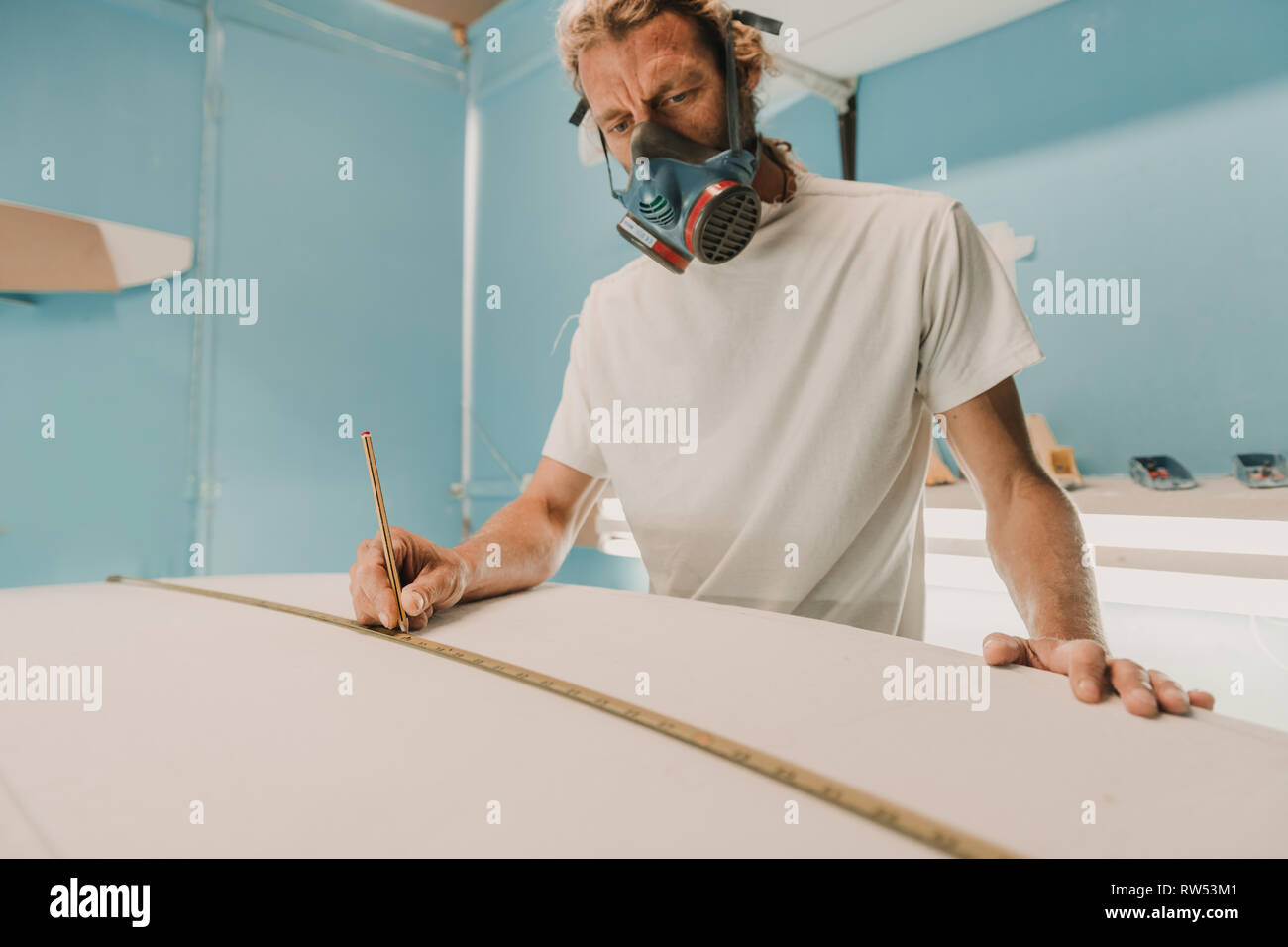 Man in respirator measuring surf board in workshop - Stock Image
