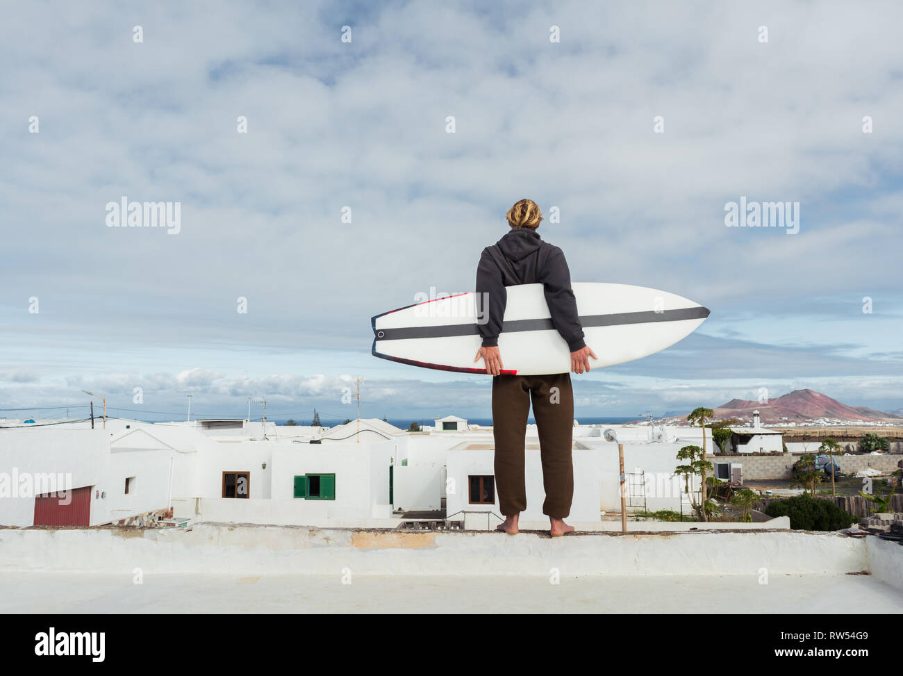 Man standing with surf board on roof of building and looking at mountain - Stock Image
