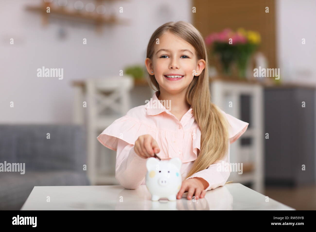 Young girl with piggybank sitting at table - Stock Image