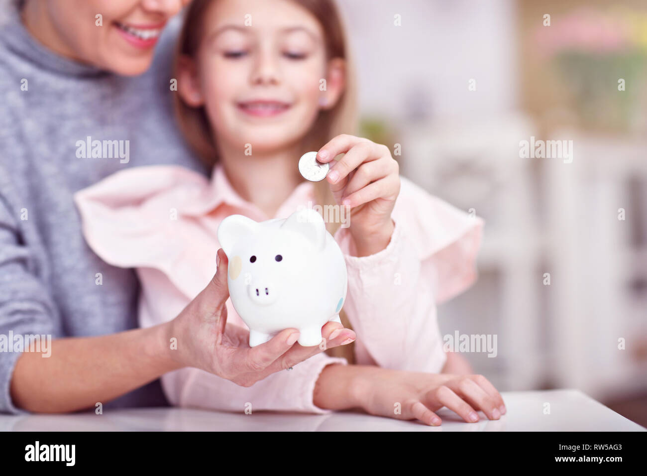 Young girl and her mother with piggybank sitting at table - Stock Image