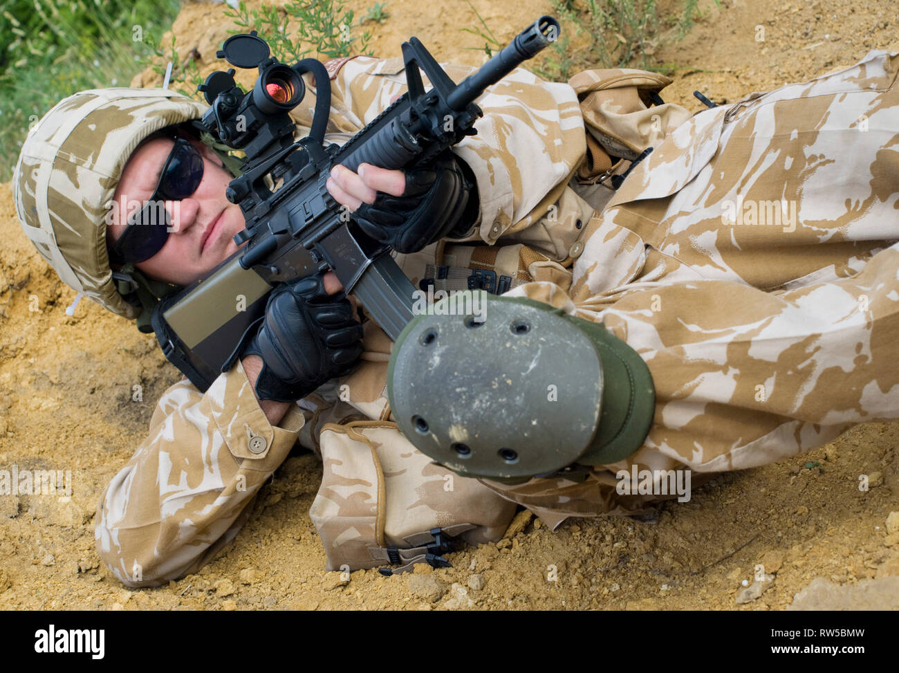 British soldier in desert uniform in action. - Stock Image