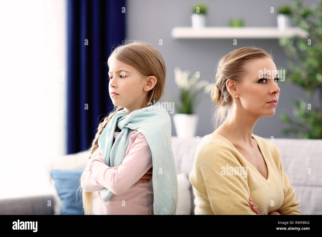 Mother and little daughter having argument at home - Stock Image