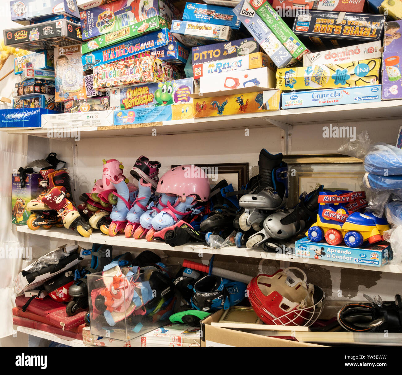 Board games, boxes of toys and roller blades in charity shop in Spain - Stock Image