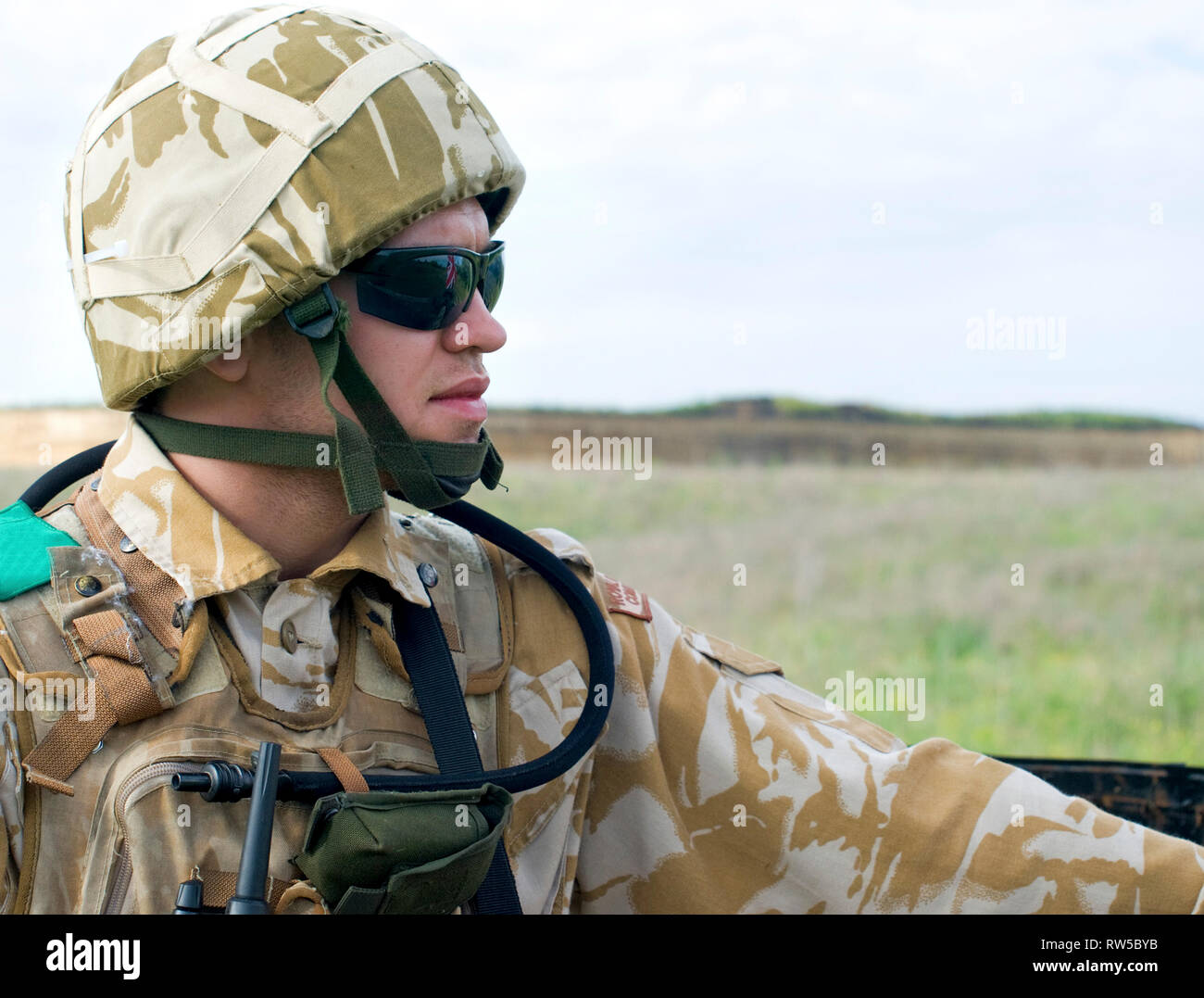 British soldier with the reflection of UK flag in glasses looking forward. - Stock Image