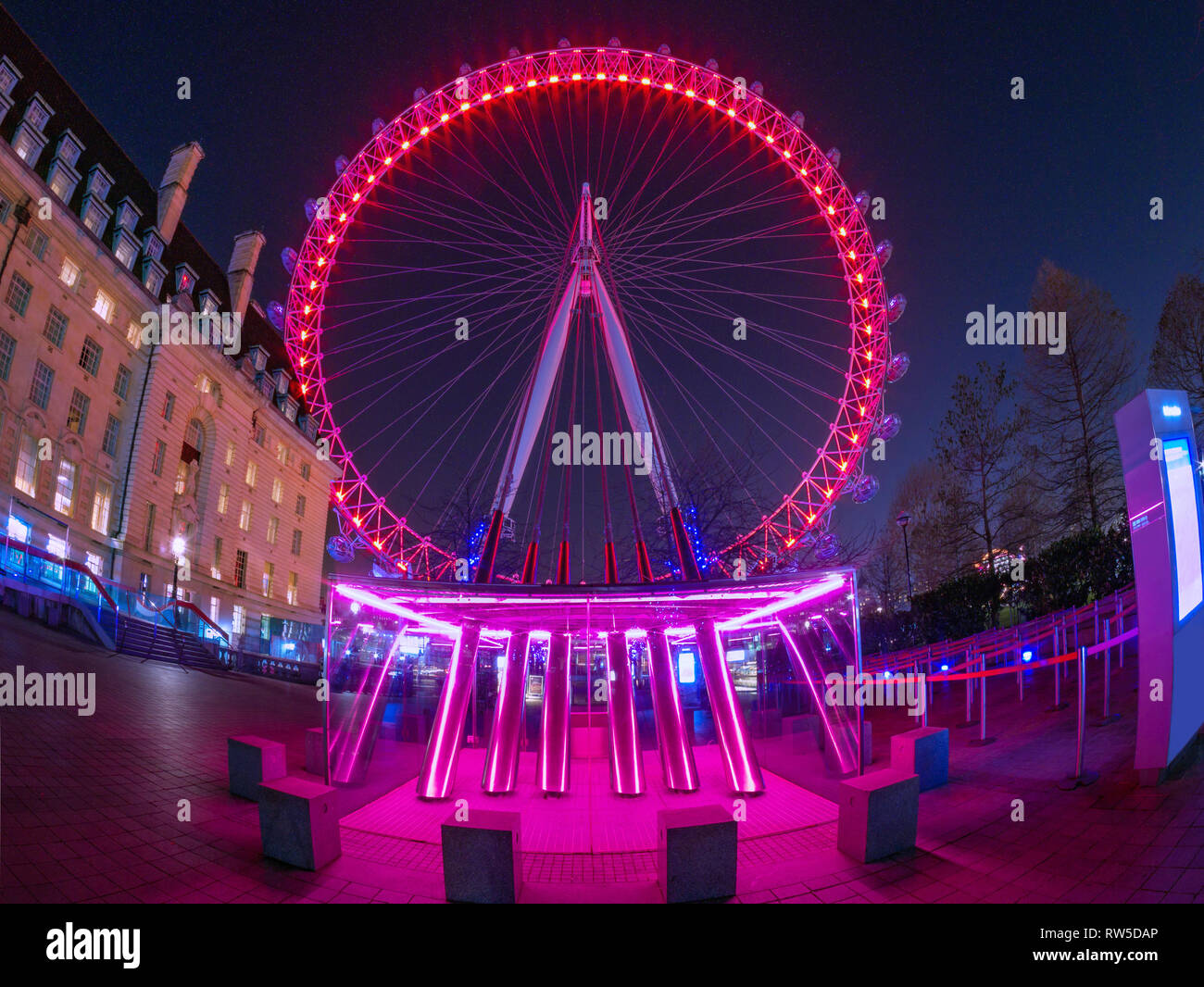 London, England, UK - February 27, 2019: Night scene with wide view of the famous London Eye against the sky full of stars, illuminated at night Stock Photo