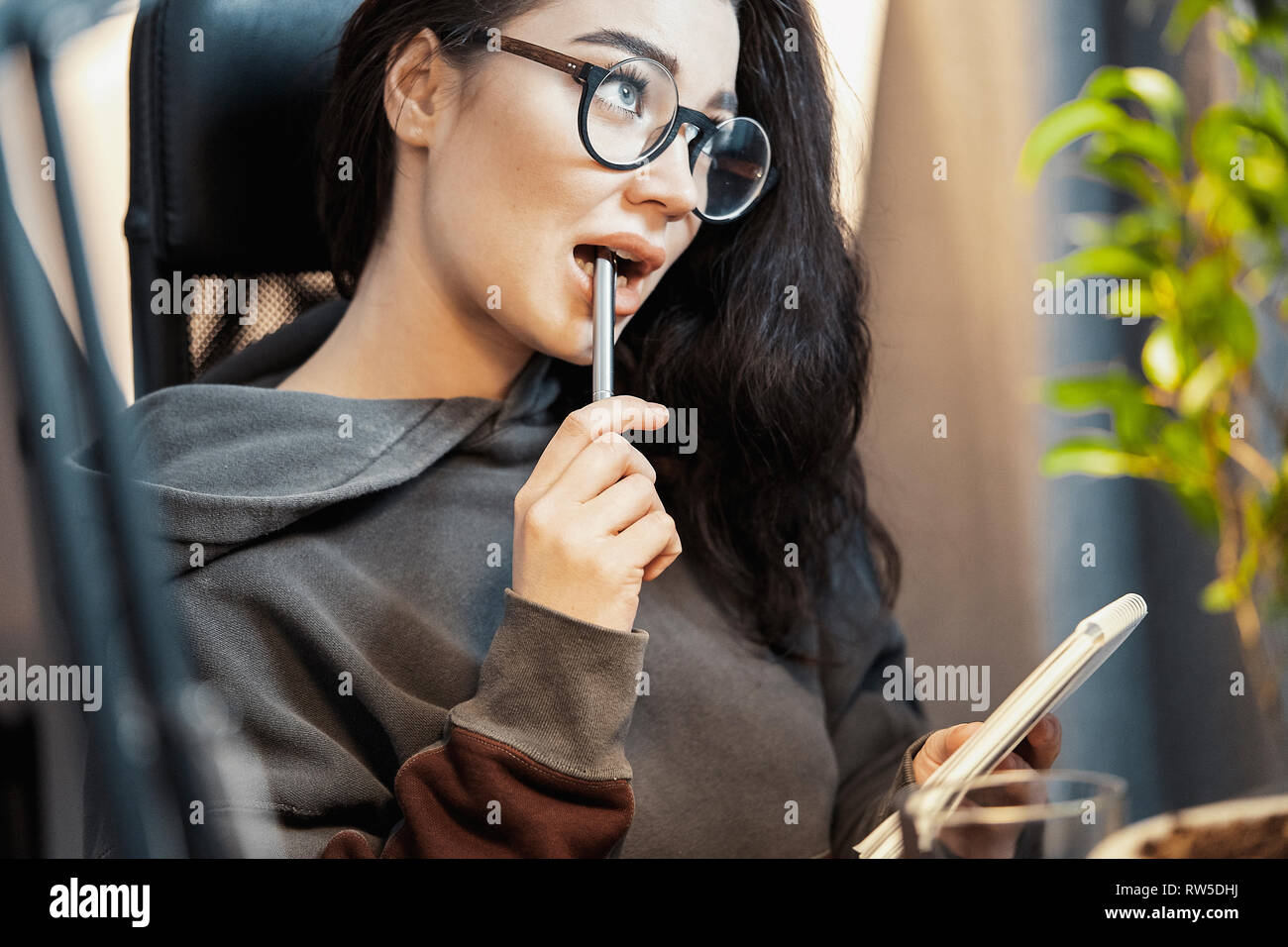 Young attractive woman freelancer writer thinking about text and writing in note pad at home. Concept of freedom and creativity. Home office. Holding  - Stock Image