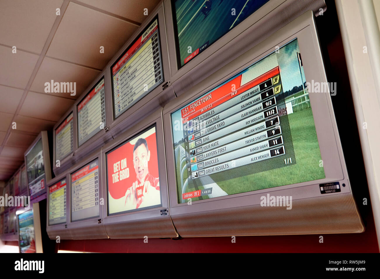 race details display screens inside a betting shop - Stock Image
