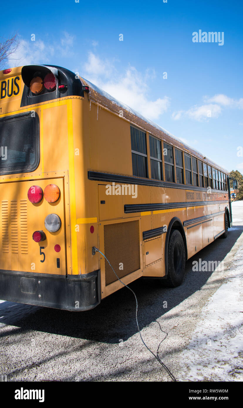 View of the side of a US bus in winter with block heater plugged in - Stock Image