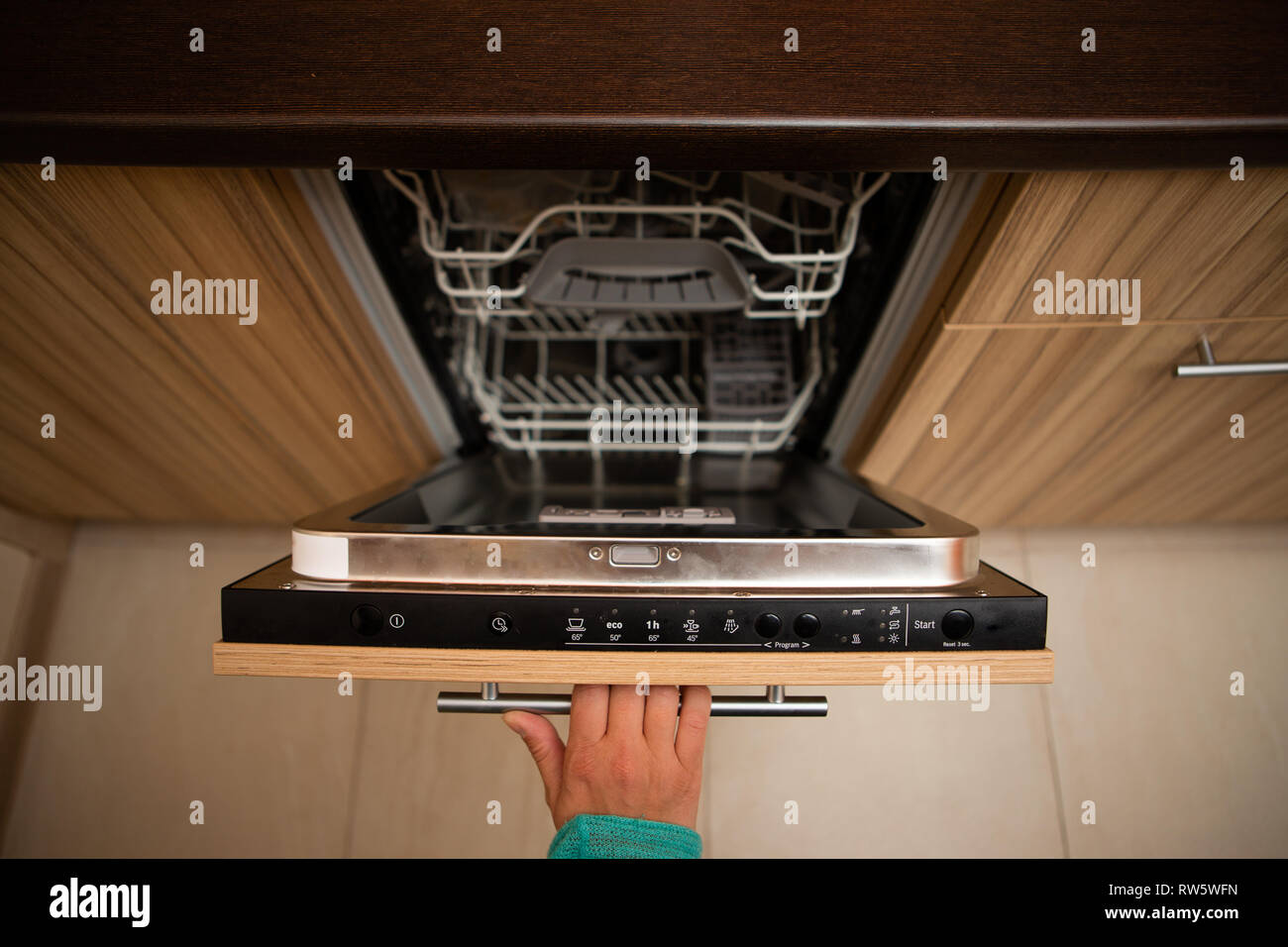 Photo of hand of man opening dishwasher in apartment Stock ...