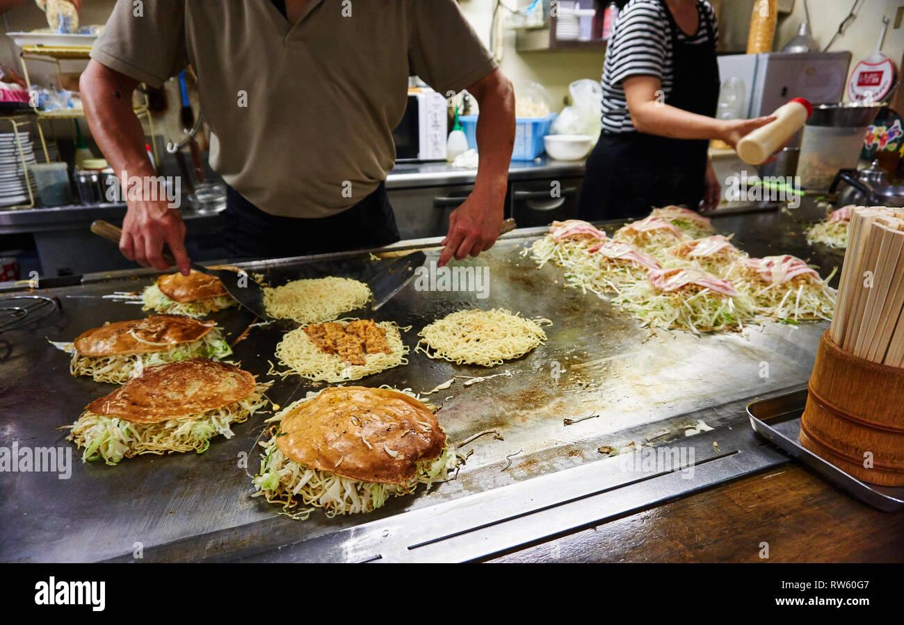 Hiroshima-style okonomiyaki Japanese savoury pancakes stuffed with yakisoba noodles are prepared by two chefs on a large griddle. - Stock Image