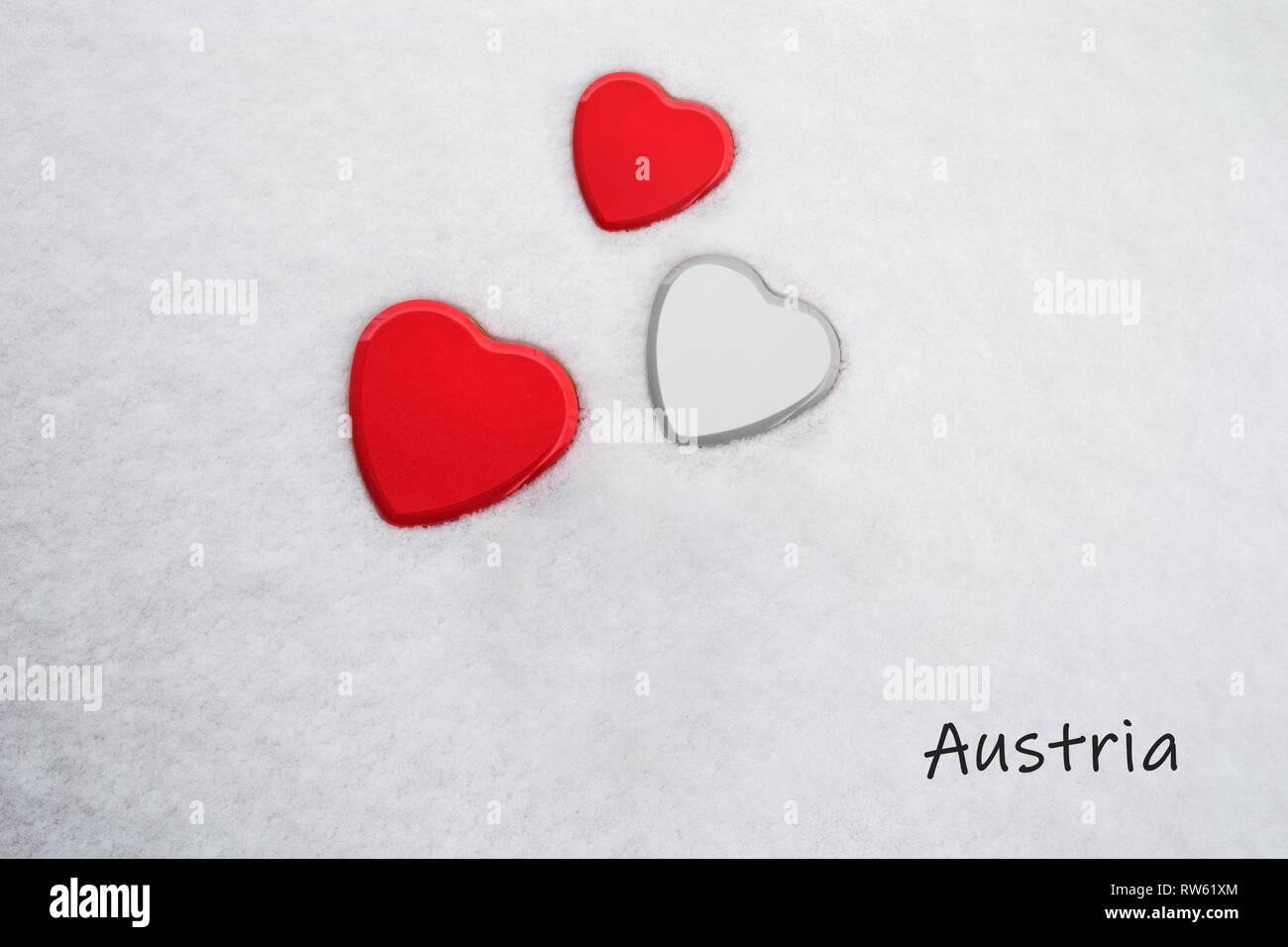 Colors of the austrian flag (Imperial Red (top/bottom) and White) painted on three hearts. Snow background with the country, Austria, written - Stock Image