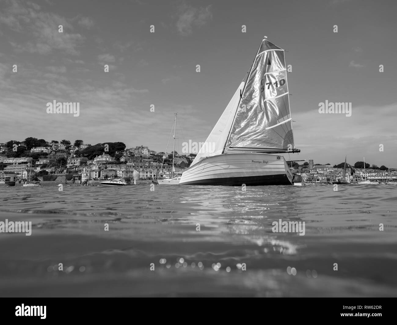 Salcombe is a hub of sailing activity in the summer. This shot was taken with a Nauticam underwater housing as the yachts sailed by. - Stock Image