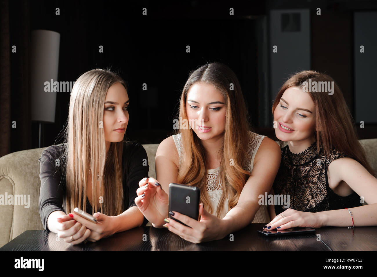 always connected, internet addiction, young girls in cafe looking at their smartphones, social network concept - Stock Image