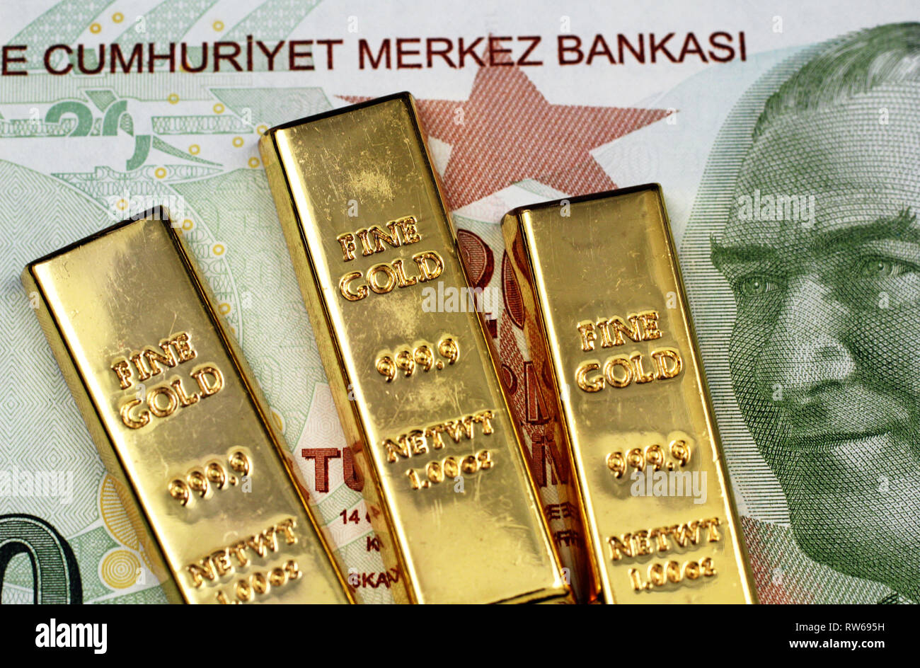 A green twenty Turkish lira bank note in macro with three small gold bars Stock Photo