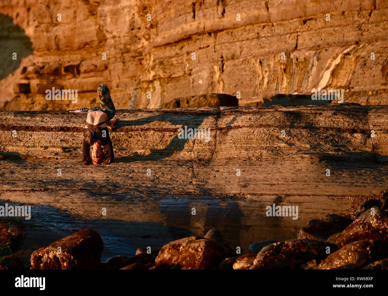 Beautiful young woman upside down in yoga pose throwing shadow on rugged cliffs at Sunset Cliffs Natural Park, Point Loma, San Diego, California, USA Stock Photo