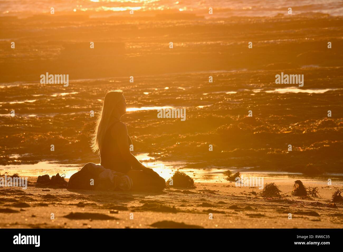 Young, blonde woman sitting and meditating on beach at sunset, at Sunset Cliffs Natural Park, Point Loma, San Diego, California, USA Stock Photo