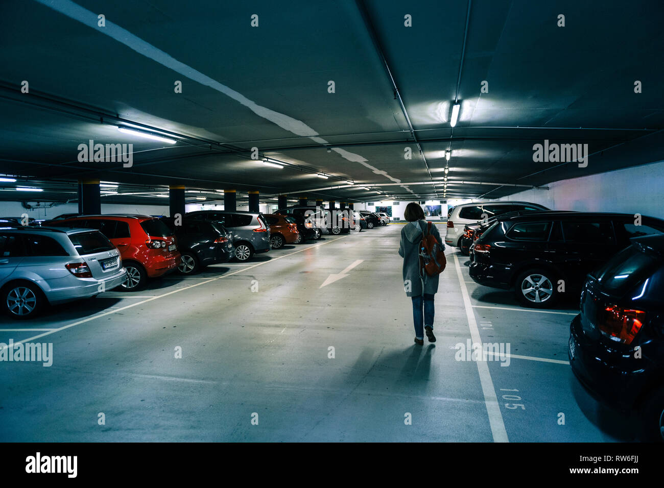 Karlsruhe, Germany - Oct 29, 2017: Rear view of German woman walking toward car in new underground parking in Schlossplatz blue tone colored parking with multiple cars parked and female dedicated area for park - Stock Image