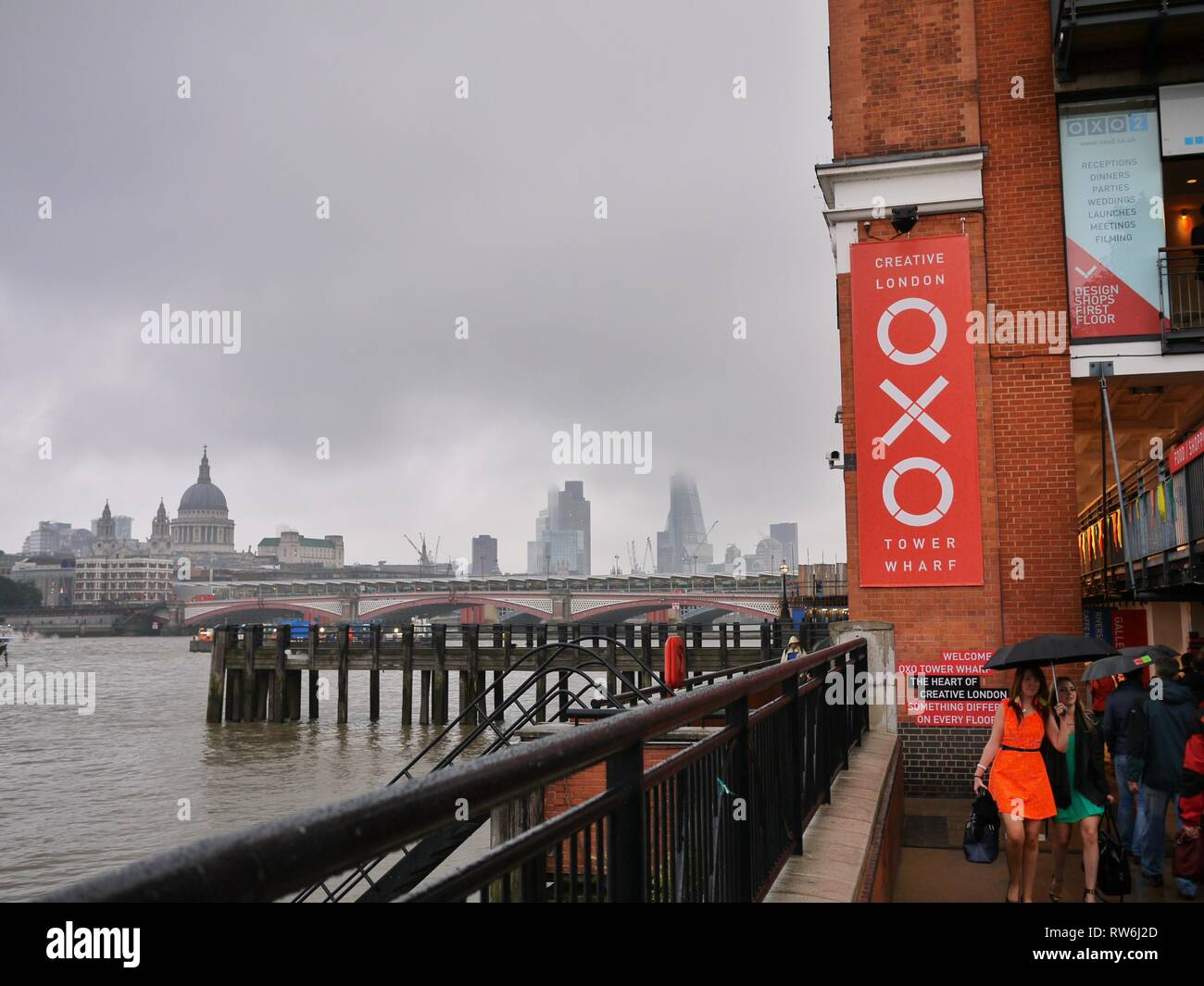 Two ladies dressed for a night out in London pass by the OXO