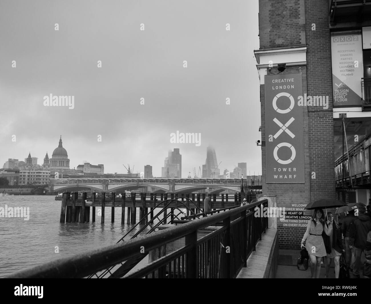 B&W image of two ladies dressed for a night out in London, passing the OXO Tower on the South Bank of the Thames, holding umbrellas against the rain. - Stock Image