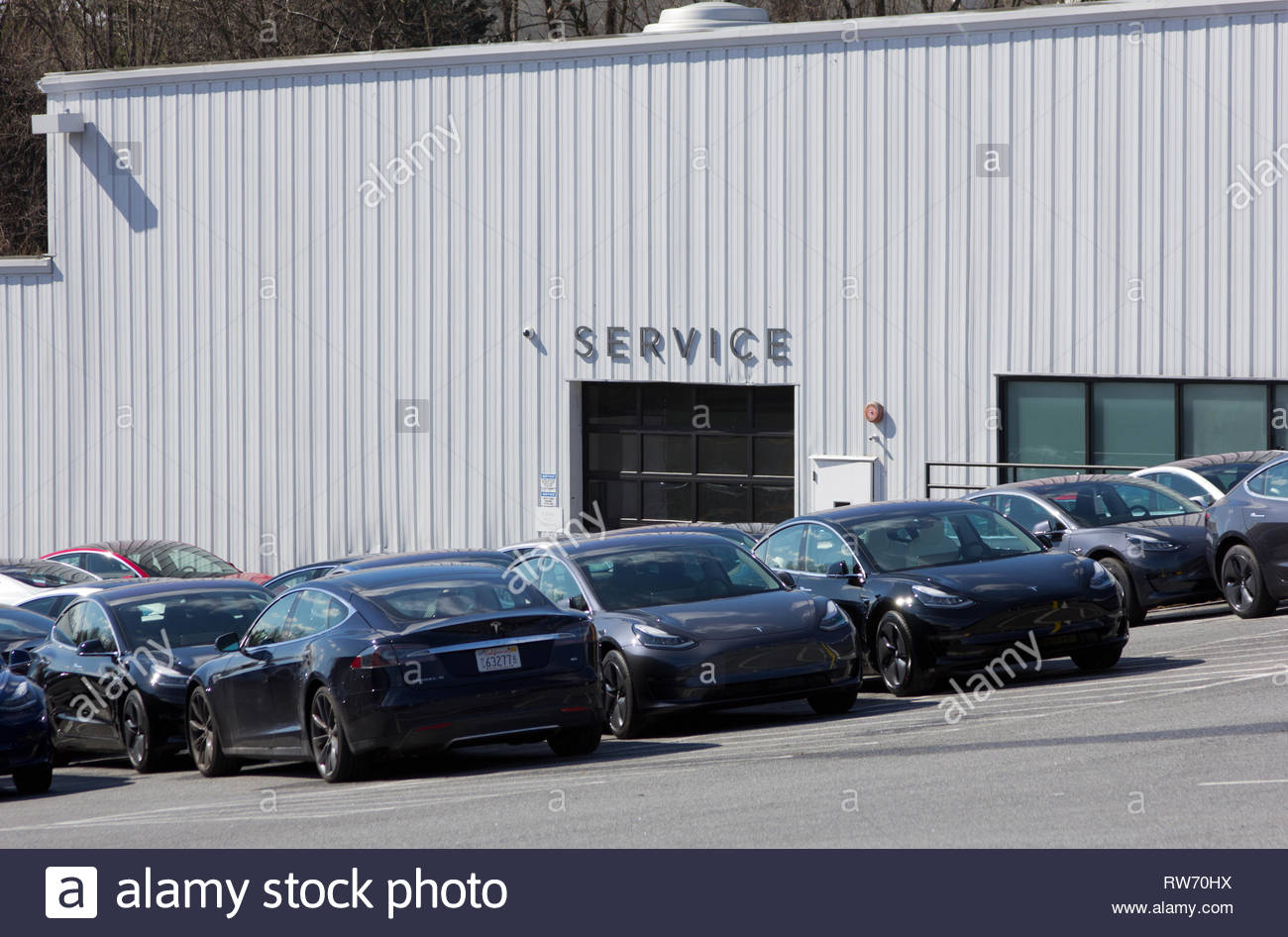 Owings Mills, Maryland, USA. 4th March, 2019. After last week's news by CEO Elon Musk that most Tesla brick-and-mortar locations would be closed as the electric automotive company transitioned solely to online sales, shares ended Monday at their lowest price since 22 October, having dropped about 11 percent since the news, and eliminating nearly $6 billion of market value. Shown is the exterior of the service department and cars on the Tesla store lot in Owings Mills, Maryland. It has not yet been indicated which of the 378 locations worldwide are slated for closure. Kay Howell/Alamy Live News - Stock Image