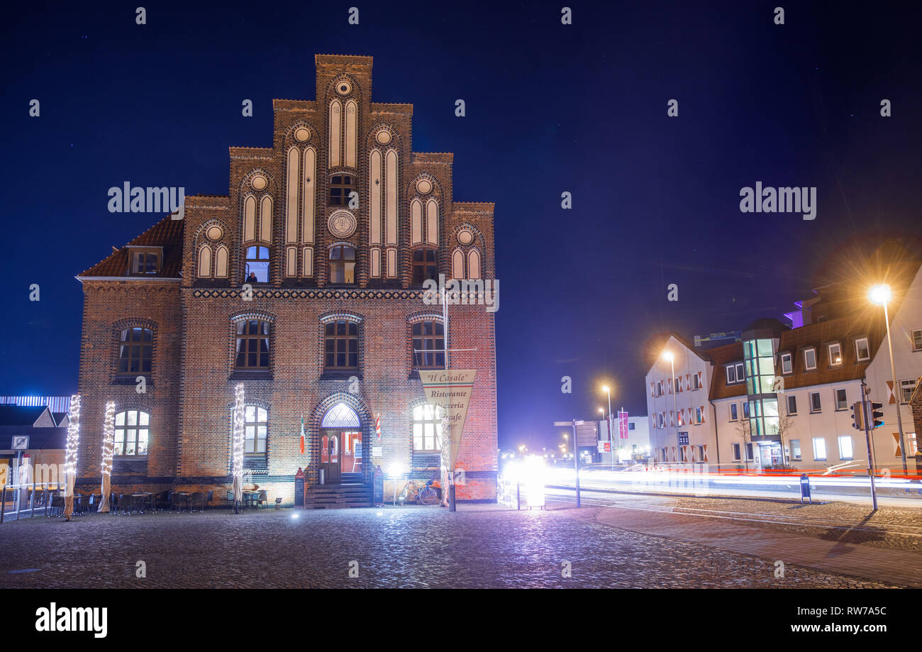 Wismar, Germany. 24th Feb, 2019. Renovated historic warehouse buildings can be seen in the city harbour after dark and are partly reflected in the water. Credit: Jens Büttner/dpa-Zentralbild/ZB/dpa/Alamy Live News Stock Photo