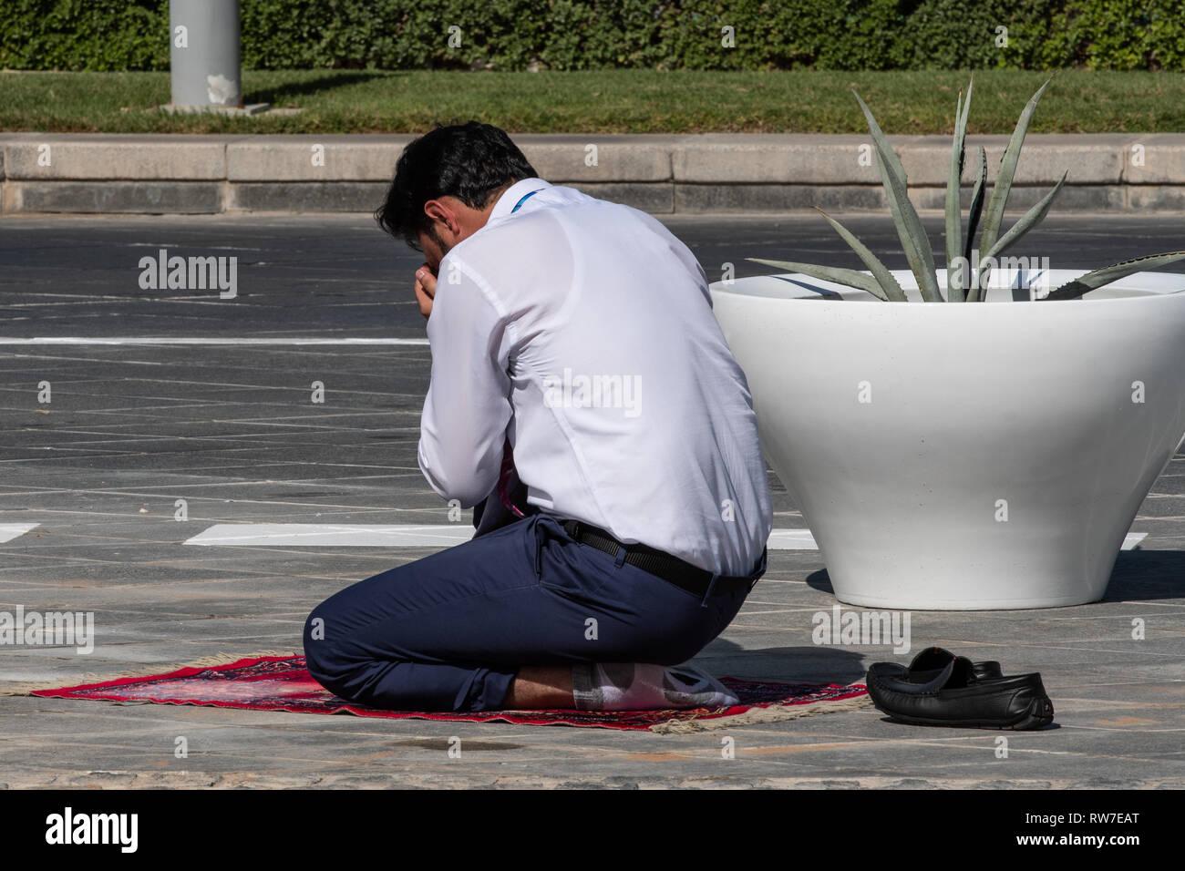 ABU DHABI, UNITED ARAB EMIRATES - 2018/12/01 - Muslim man praying in the middle of the street in Abu Dhabi. - Stock Image