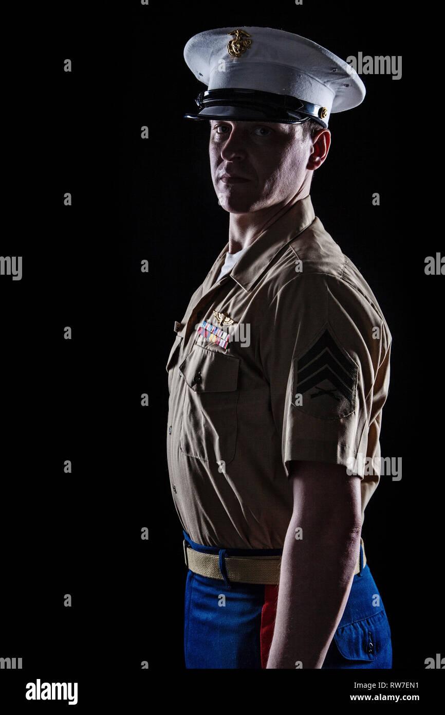 Contour shot of U.S. Marine in blue dress uniform on black background. - Stock Image