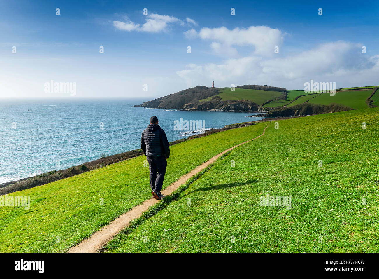 Walking the South West Coast Path from Fowey to Gribbin Head on an unseasonaly warm February day. I'm the person in the photo & allow commercial usage. - Stock Image