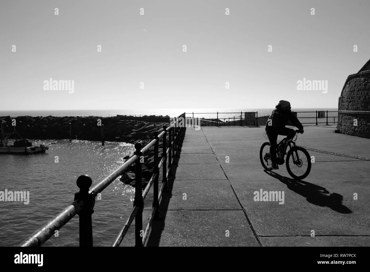 A cyclist on the seafront at Ventnor Harbour, Ventnor, Isle of Wight, England, UK. - Stock Image