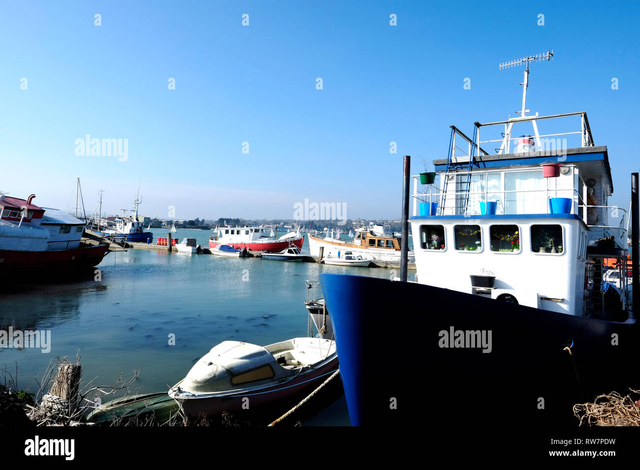 View from the road of houseboats at high tide moored in Bembridge Harbour, Bembridge, Isle of Wight, England, Britain, UK. - Stock Image