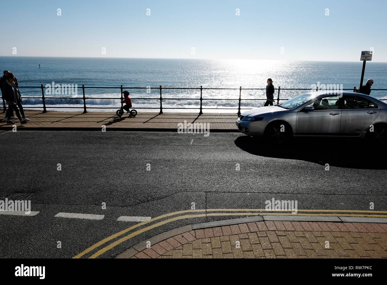 Adults and children, one riding a bicycle, promenade along the seafront in winter, at Ventnor, Isle of Wight, UK. - Stock Image