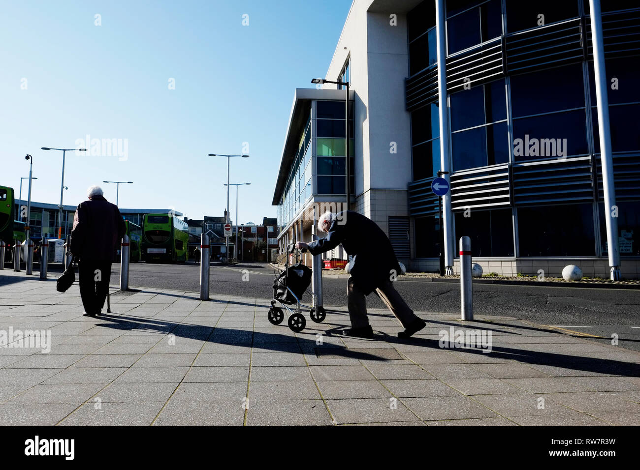 An old man, stooped over, pushes his shopping cart uphill into the central bus station at Newport, Isle of Wight, UK. - Stock Image
