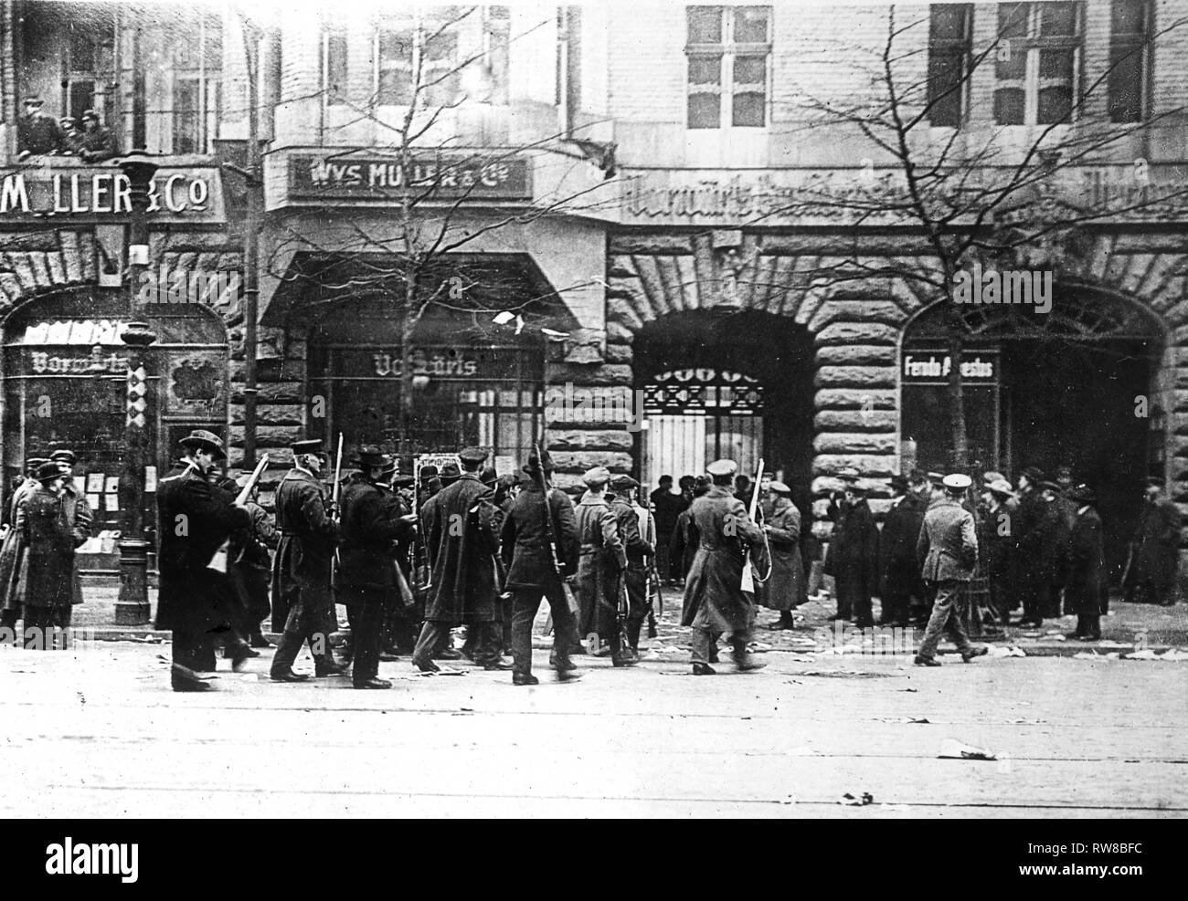"Revolution in Berlin, Germany. Group of Sparticists, armed with rifles, taking possession of building of Berlin newspaper ""Vorwaerts."" ca. 1919 Stock Photo"