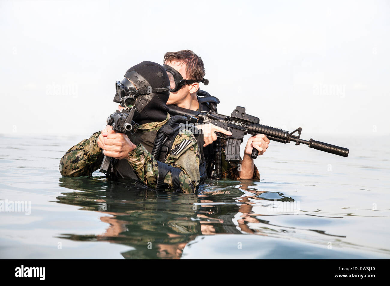 Navy SEAL frogmen with complete diving gear and weapons in