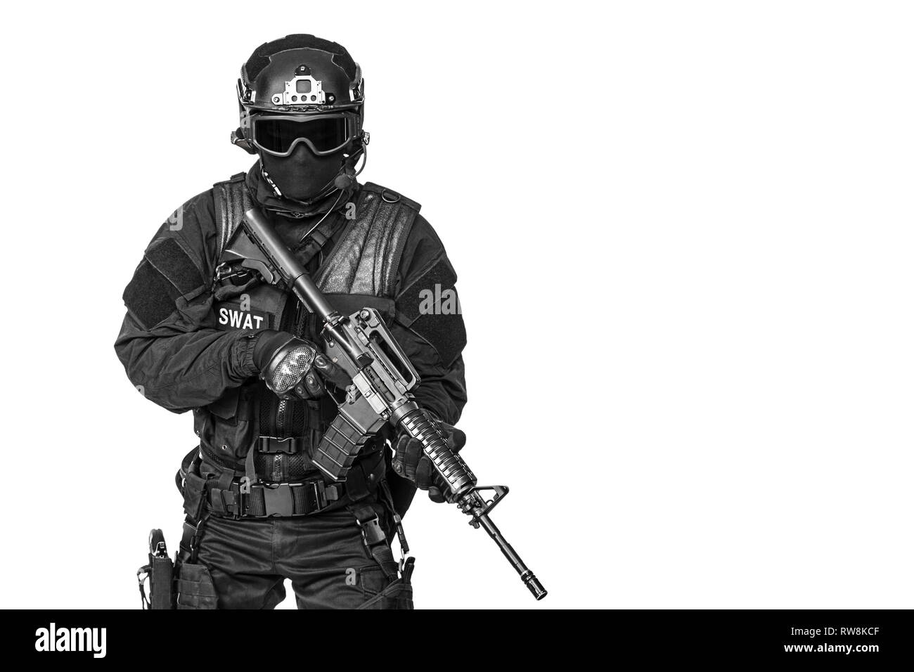 Spec ops police officer SWAT in black uniform and face mask, studio